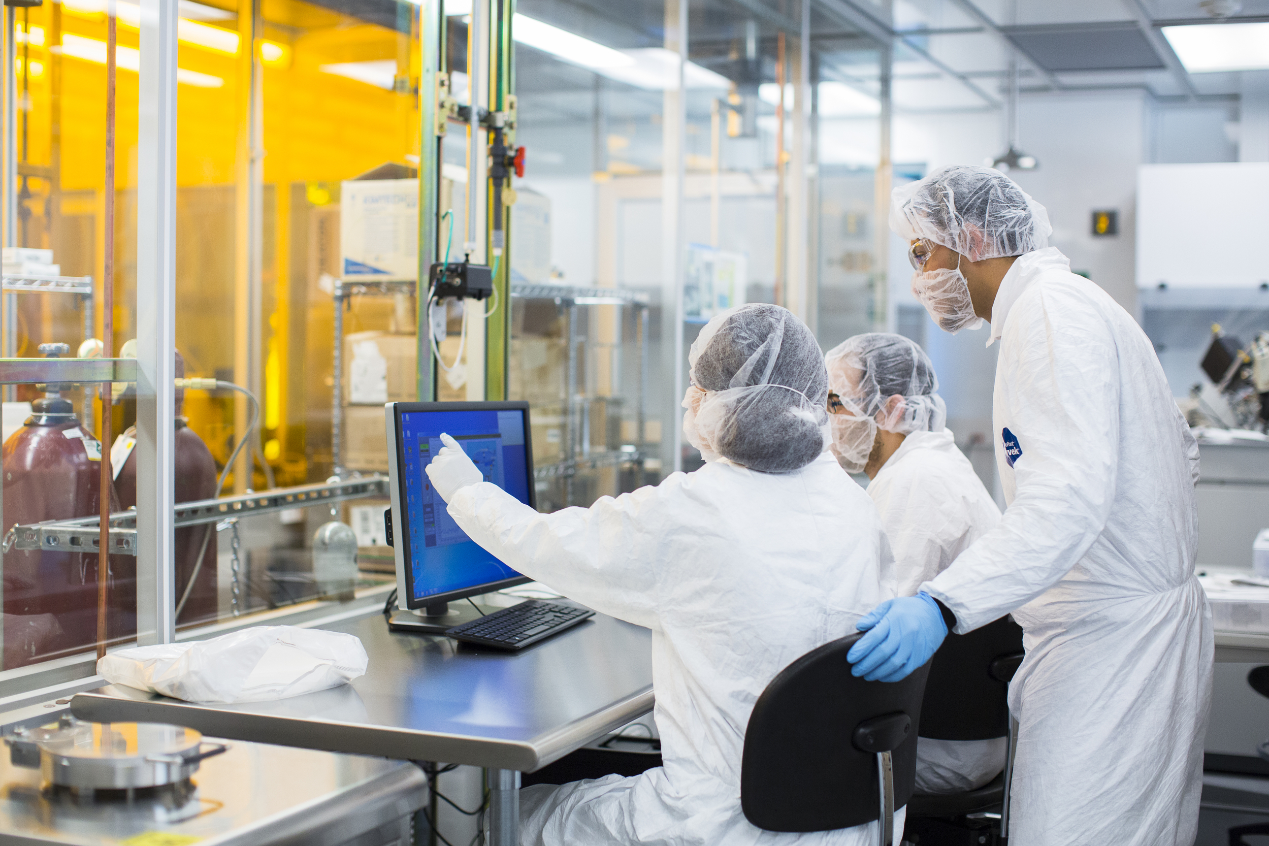 Stem cell laboratory with researchers reviewing information on computer monitor.